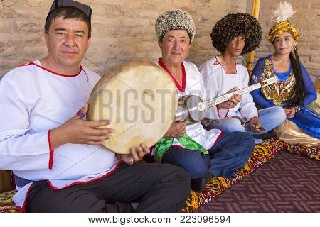 KHIVA, UZBEKISTAN - MAY 24, 2016: Khorezmian musicians in traditional dresses play and sing  local songs.