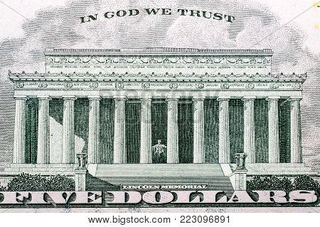 Closeup of a five dollar bill; Lincoln Memorial.
