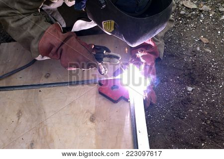 A strong man is a welder in a black T-shirt, in a welding mask and welders leathers, a metal product is welded with a welding machine in the garage, blue sparks fly to the