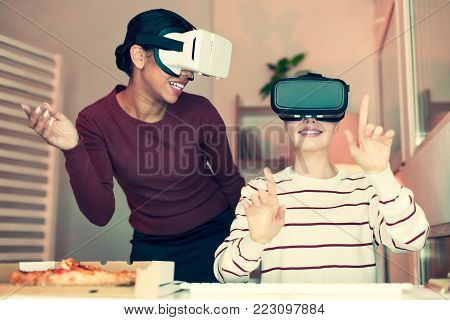 Enjoying themselves. Two happy female best friends wearing VR headsets and playing games, having fun during small home party