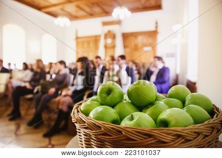 In foreground there are green apples, in background Hall for conference people are sitting. Concept youth, freshness, unity, business, learning