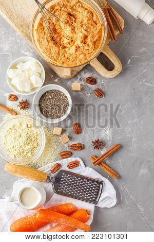 Healthy baking of carrot cake, vegan dessert ingredients: dough in a bowl, chia, coconut butter, almond milk, nuts. Carrot bread, gray background.