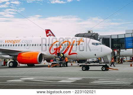 Santos Dumont Airport, Rio de Janeiro, Brazil - Dec 22, 2017: Airport workers at Rio de Janeiro's Santos Dumont Airport pick up passengers' luggages from a Gol airliner airplane