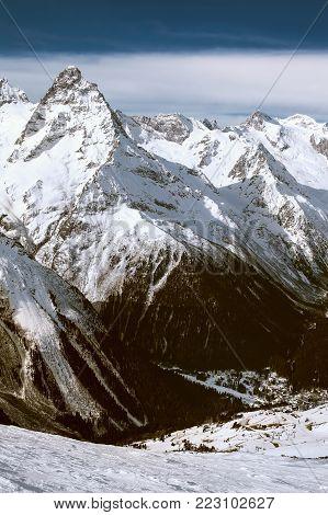 Snowy mountains in clouds at sun day. Caucasus Mountains, mount Belalakaya, ski resort Dombay.