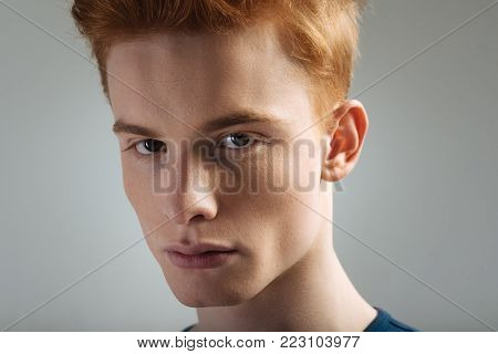Beautiful eyes. Attractive earnest dark-eyed young man wearing a t-shirt and staring and having red hair
