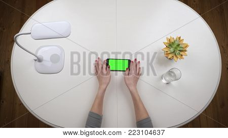 Woman freelancer takes a smartphone and typing using app. Chroma key Green screen. Top view. Hands close up view.