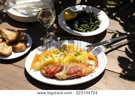 Cooked fresh red scorpionfish sarved with boiled potatoes on white plate near glass of white wine, greens salad dish, bread and plates on wooden table in greek tavern. Horizontal. Close-up.