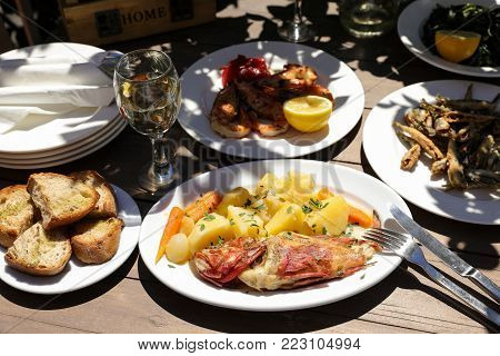 Cooked fresh red scorpionfish sarved with boiled potatoes, shrimps cooked on grill, fried fresh anchovies, glass of white wine, greens salad dish, bread and plates on wooden table in greek tavern.
