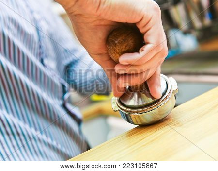 barista presses the Holder to press the coffee in the holder