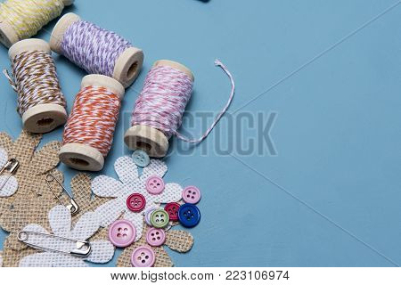Arts and crafts background image of colourful twine with buttons and safety pins, taken with copy space