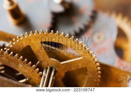 Cog gear wheel mechanic machinery ornament on vintage textured paper background. Retro technology parts closeup, aged clockwork details.