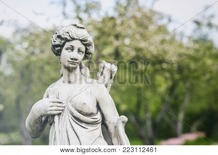 Old white sculpture, Diana, goddess of hunt, moon, and nature, female hunter with bow and arrow, was equated with Greek goddess Artemis.