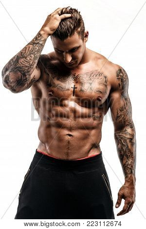 Shirtless muscular tattooed man isolated on white background.