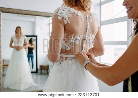 Smiling african woman shopping for wedding outfit in bridal boutique. Bride choosing white gown at shop of wedding fashion.