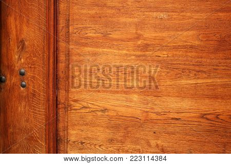 Detail of old wooden door with redness wood texture and metal rivets