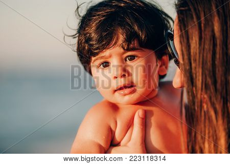 portrait of a beautiful baby boy playing on the shoreline with his mother