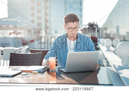 Diligent student. Smart gentleman wearing casual attire sitting on a terrace of a cafe and focusing his attention on a screen of a laptop while doing his home assignment.