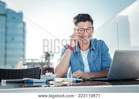 Positivity is the key to success. Waist up shot of a cheerful self employed man sitting at his laptop and looking into the camera with a broad smile on his face while working in a cafe.