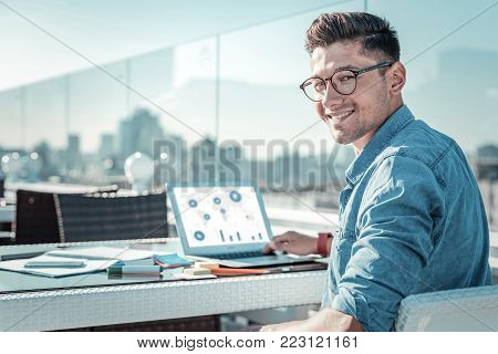 Smart and educated. Joyful male student looking into the camera and grinning broadly while sitting on a terrace and preparing his home assignment.