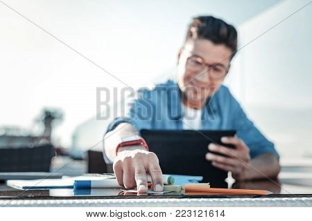 This worth noting. Selective focus on a hand of a guy in casual reaching for a sticky note while sitting outdoors and working on his touchpad.
