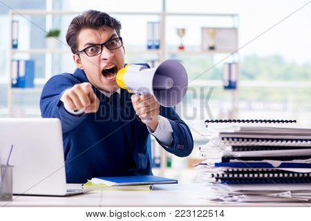 Angry aggressive businessman with bullhorn loudspeaker in office