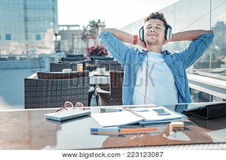 No time for worries. Joyful self employed gentleman in casual holding hands behind his head and smiling while listening to music after working long hours outdoors.