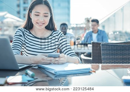 Getting updated. Relaxed young lady reading news on her smartphone and smiling while working on her home assignment outdoors.