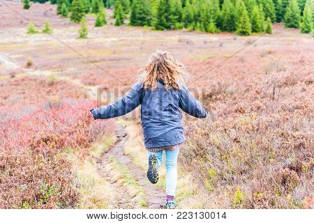 Young athletic, fit, free happy woman running in autumn, fall season meadow field path hike in mid-air