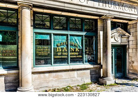 Thurmond, USA - October 19, 2017: Abandoned closed retro vintage building with National Bank sign in West Virginia ghost town village closeup