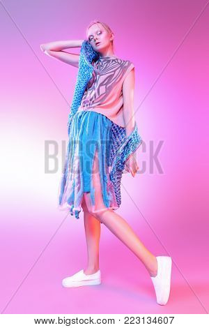 Vogue shot of a female model posing at studio. Fashion collection. Full length portrait over pink background. poster