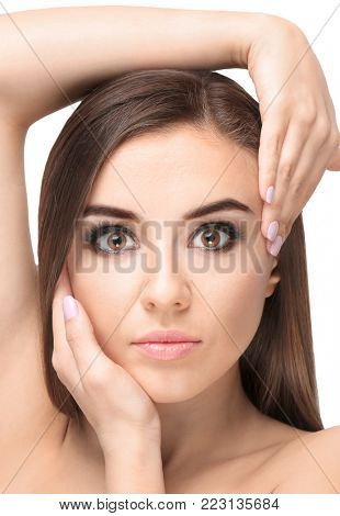 Beautiful young woman with eyelash extensions on light background