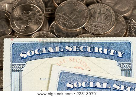 USA Social security cards laid on pile of quarter coins to illustrate money in retirement