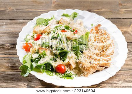 Caesar Salad with parmesan cheese and croutons. Grilled chicken breasts and fresh romaine lettuce in plate.