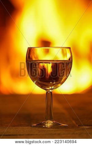 Glass of white wine against cozy fireplace background, winter vacation, winter vacation, in country house, horizontal.