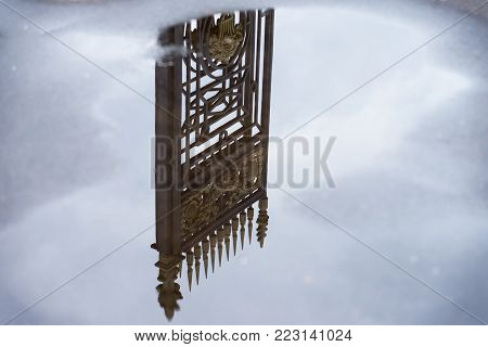 Old decorative iron fence reflected in puddle among the blue sky with clouds after rain. Concept dream, paradise, nostalgia, romantic mood, unreality, otherworldly, Sur