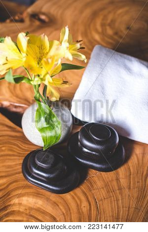 A view from above of yellow flowers in a vase and stones for stone therapy. Yellow daffodils and stones for massage lie on a wooden table. White towels lie in the background.
