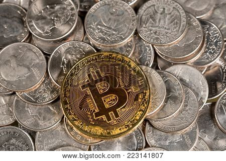 Single golden bitcoin coin laid on loose change of US quarters
