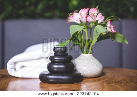 Dark stones for massage are stacked on top of each other on the table. White-pink daffodils stand in a white vase. Pyramids of stones for massage lie on the wooden table. White towels lie in the background.