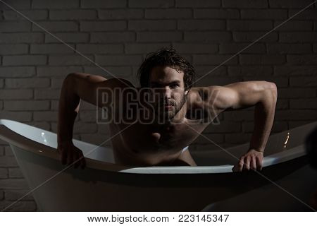 Hygiene and healthcare. Spa and relaxation, sexy man. Bathroom and home comfort. Man with muscular body in bath. Guy with wet hair sitting in bath tub.