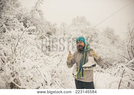 Man in thermal jacket, beard warm in winter. Temperature, freezing, cold snap, snowfall. Winter sport and rest, Christmas. skincare and beard care in winter. Bearded man with skates in snowy forest.