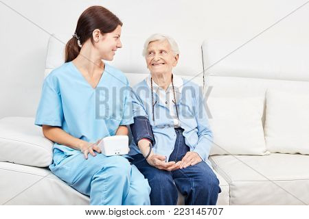 Young nursing assistant and senior citizen as a patient in blood pressure measurement for prevention
