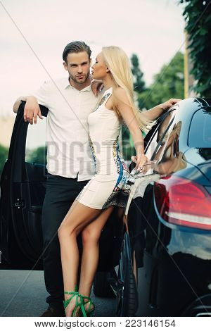 Sensual woman and man at auto outdoor. Sexy couple at car on summer day. Business trip, travel, business concept. Transport, transportation, vehicle. Luxury lifestyle, style. Date, love, romance.