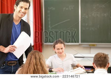 Teacher standing while math lesson in front of a blackboard and educate or teach students or pupils or mates in a school or class