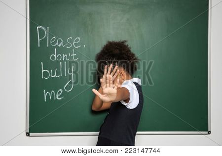 African-American girl near chalkboard with text