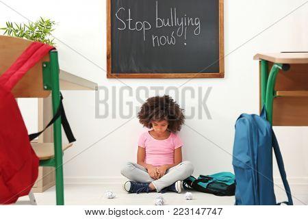Sad African-American girl sitting on floor in classroom