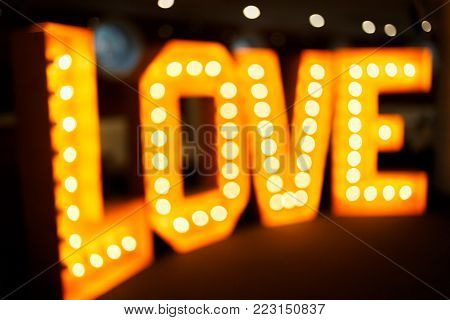 Valentines day background. Love word made of glowing light bulbs in bokeh. Caption word love for Valentines day, love inscription from the light.