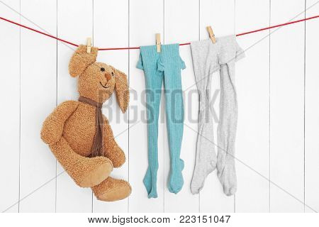 Children's tights and toy on laundry line against wooden background