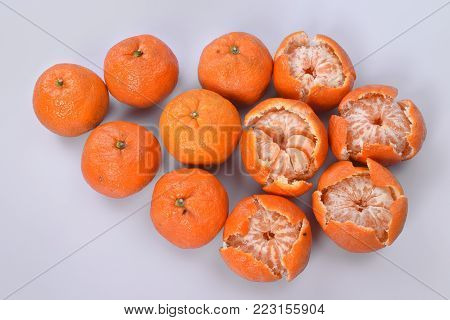 Large round orange mandarins on a light gray background, on the left are fruits with whole peel, on the right near the fruit peel is brushed.