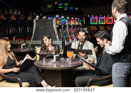 Group of friends looking at some menus and ordering some food to a waiter in a casino