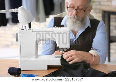 Senior tailor working on sewing machine in atelier poster